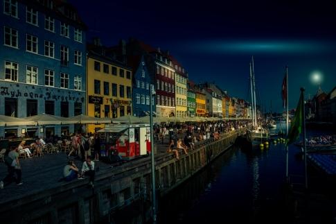 People enjoying the warm evening in Nyhavn, Copenhagen.